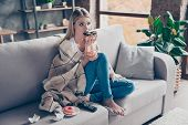 Beautiful Blonde Woman Sitting On Couch In Living Room Under Blanket Eating Chokolate Donat Watching poster