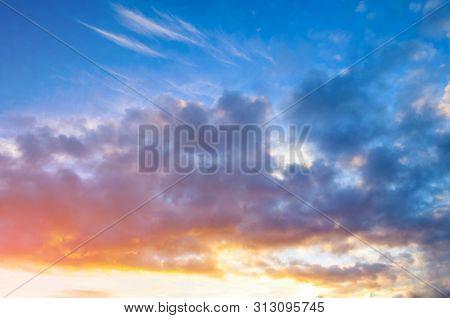 poster of Sunset sky background - pink, orange and blue dramatic colorful clouds lit by evening sunset light. Vast sunset sky landscape scene