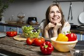 Young Cheerful Girl Prepares A Vegetarian Salad In The Kitchen, She Sits At The Table With Food And  poster