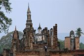 Male Tourist In East Headscarf Is Looking On Big Budda Statue Famous Sukhothai Historical Park, A Un poster