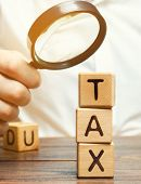 Wooden Blocks With The Word Tax And A Magnifying Glass In The Hands Of A Businessman. The Concept Of poster