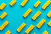 Flat Lay Image Of Yellow Blocks From Child Constructor. Bright Plastic Blocks On Turquoise Blue Back poster