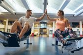 Low angle view of young fit Caucasian male and female athlete giving high five in fitness center. Br poster