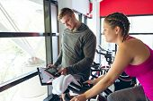 Front view of young Caucasian Male trainer assisting young Caucasian female athlete with exercise in poster