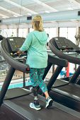 Rear view of disabled active senior Caucasian woman with leg amputee exercising on treadmill in fitn poster
