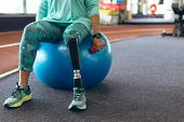 Low section of disabled active senior Caucasian woman with leg amputee exercising with dumbbell whil poster