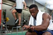 Front view of handsome young African-american male athletic checking time on watch in fitness center poster