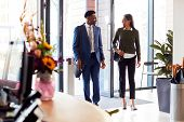 Businessman And Businesswoman Arriving For Work At Office Walking Through Door poster