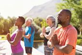 Four senior people meditating with joined hands and closed eyes breath deeply. Multiethnic class of  poster