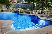 stock photo of hot-tub  - Residential inground swimming pool in backyard with waterfall and hot tub - JPG