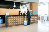 Businessman Making Booking At Front Desk With Latin Receptionists In Hotel Lobby poster