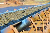 stock photo of porphyry  - ore conveyor shoot on sunset inside of plant - JPG