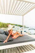 Young Beautiful Woman Wearing Hat And Pareo Sitting On Sunbed poster