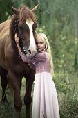 Innocent Blonde Girl With Horse In Forest. Beautiful Caucasian Girl With Long Blonde Hair In A Pink  poster