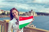 Happy Young Redhead Hungarian Urban Woman Holding Hungarian Flag At Budapest, Toothy Smile poster