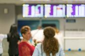 Tourists Stand In Front Of An Information Board In The Interior Of The Airport. Blur Image Of People poster