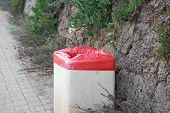 Garbage Bin With Red Packet On The Street. Trash Can On A City Street.trash Can On The Street In The poster