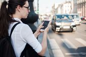 Call A Taxi Using The Mobile Application. A Young Woman In The City Is Standing Near The Road With A poster
