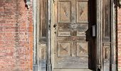 Old weathered wood door in brick wall