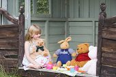 pic of tea party  - Young girl having tea party with stuffed toys in home garden - JPG