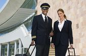 stock photo of air hostess  - Portrait of happy pilot and air hostess standing together with luggage at the airport - JPG