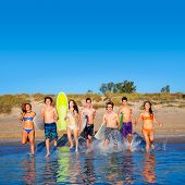 Teen surfers boys and girls group running happy to the beach splashing water