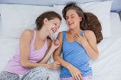 stock photo of slumber party  - Girls wearing pajamas lying in bed and laughing at slumber party - JPG