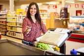 pic of cash register  - Beautiful young woman at the cash register of a supermarket paying with a credit card and smiling - JPG