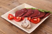 image of flank steak  - fresh raw beef meat steak fillet on wooden plate with asparagus and tomatoes ready to prepare - JPG