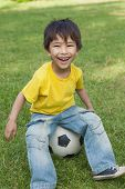 Full length portrait of a cute little boy sitting on football at the park