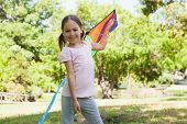 Portrait of a happy young girl holding kite at the park