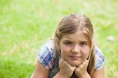Close-up portrait of a cute young girl lying on grass at the park