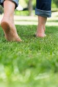 Low section of woman walking on grassy land in a park