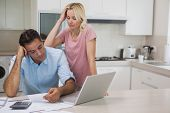 Unhappy couple with bills and laptop in the kitchen at home