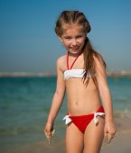 happy cute little girl in red-and-white swimsuit on the beach