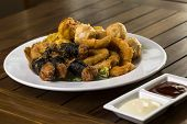 foto of wanton  - A hortizontal shot of a plate of fried finger food snack ready to be served - JPG