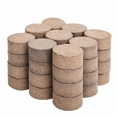 stock photo of briquette  - Peat briquettes for growing seedlings isolated on white with clipping paths - JPG