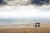 image of loneliness  - Empty wooden bench on the beach in cloudy weather - JPG