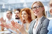 Group of happy business people applauding at conference with smiling blonde in front