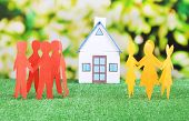 Little house and paper people on green grass, on bright background