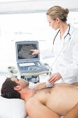 Female doctor using sonogram on male patient in examination room