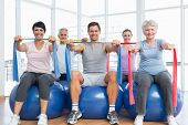 foto of senior class  - Class holding out exercise belts while sitting on fitness balls in yoga class - JPG