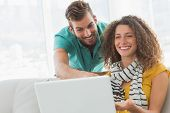 Smiling woman on the couch showing her co worker her laptop in creative office