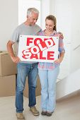 Happy couple standing and holding sold sign in their new home