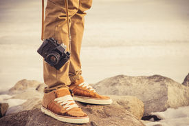 stock photo of foot  - Feet man and vintage retro photo camera outdoor Travel Lifestyle vacations concept  - JPG