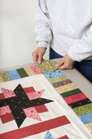 image of cornerstone  - A quilter arranges a square of fabric for the cornerstone of a quilt top border - JPG