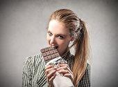 stock photo of greedy  - beautiful woman is eating a chocolate bar - JPG