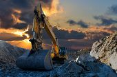 pic of earth-mover  - Image of a tracked excavator in a quarry with a setting sun and light rays - JPG