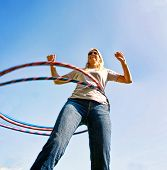 pic of hula hoop  - a woman hula hooping on a clear day  - JPG
