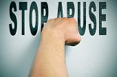 foto of racial discrimination  - a man punching the text stop abuse - JPG